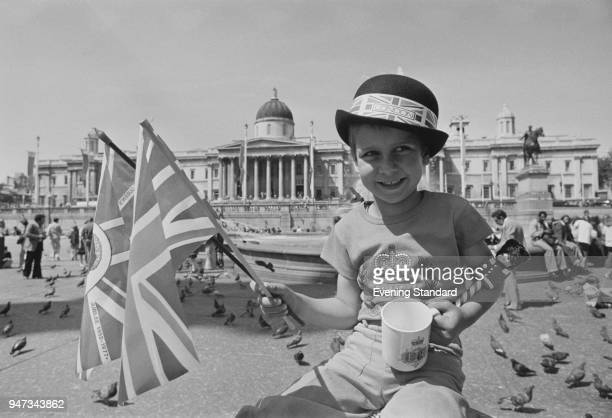 Thorsten Wussow holding two British flags and a cup with the jubilee logo celebrates the Silver Jubilee of Queen Elizabeth II in Trafalgar Square...