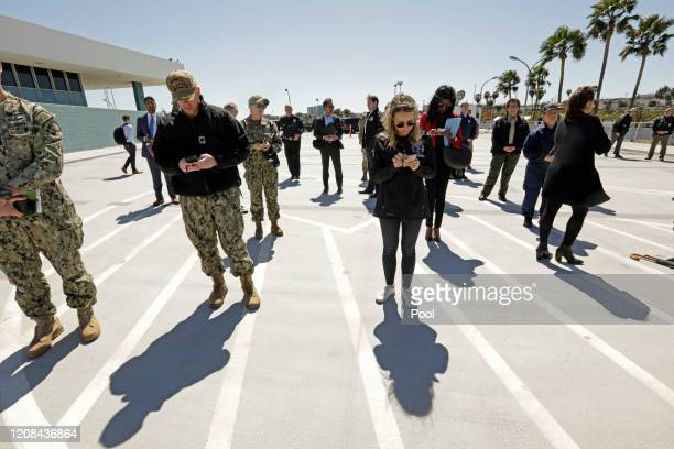 Those attending the press conference at the hospital ship USNS Mercy keep the appropriate distance as they listen to California Governor Gavin Newsom...