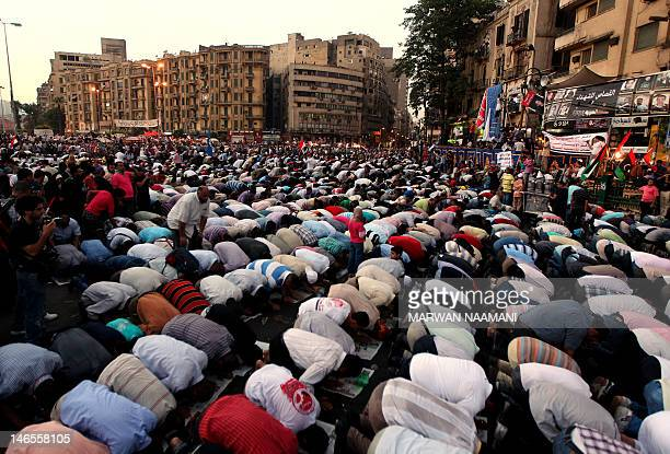 Thosuands of Egyptian supporters of the Mulsim Brotherhood presidential candiade Mohammed Mursi perform dusk prayers at Cairo's Tahrir Square June 19...