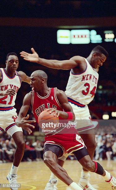 Though grounded, Air Jordan, of the Chicago Bulls, eludes two New York Knicks, Gerald Wilkins and Charles Oakley , as he heads for the basket during...