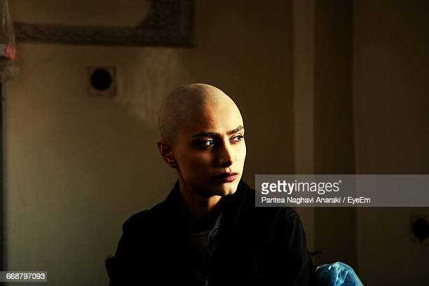 thoughtful bald young woman with cancer at home - hair loss stock pictures, royalty-free photos & images