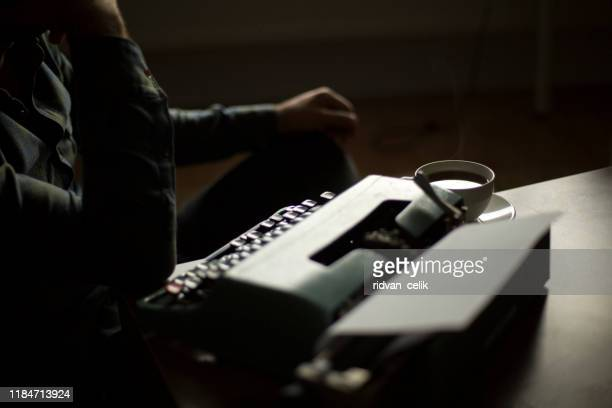 thoughtful bearded stylish writer typing on typewriter - literature stock pictures, royalty-free photos & images