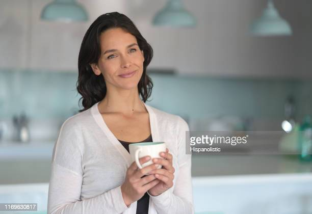 Thoughtful beautiful woman at home enjoying a coffee looking away slightly smiling