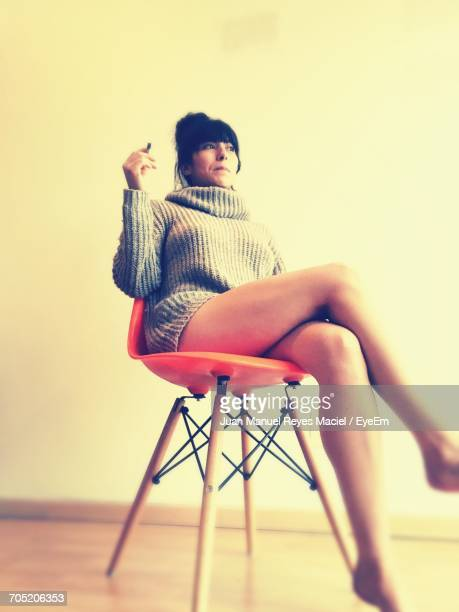 Thoughtful Beautiful Woman Sitting On Chair At Home