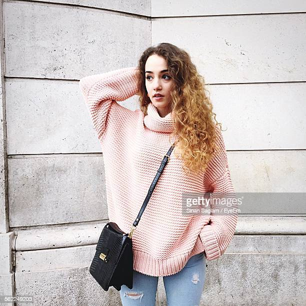 thoughtful beautiful woman standing against wall - shoulder bag stock pictures, royalty-free photos & images