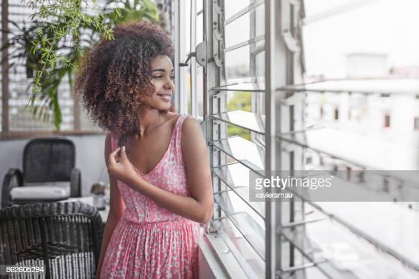 Thoughtful beautiful woman standing by window
