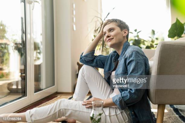 thoughtful beautiful woman with short hair sitting by armchair at home - short hair stock pictures, royalty-free photos & images