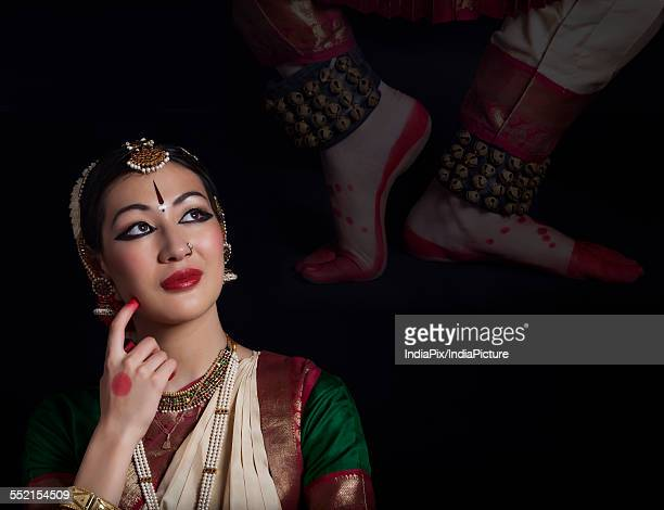 Thoughtful Bharatanatyam dancer over black background