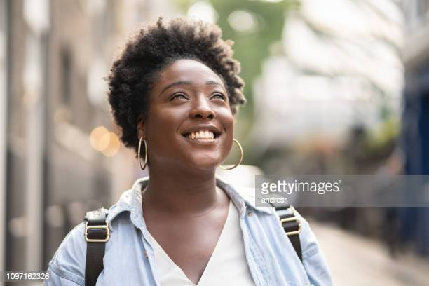 thoughtful black woman looking happy on the street - introspection stock pictures, royalty-free photos & images
