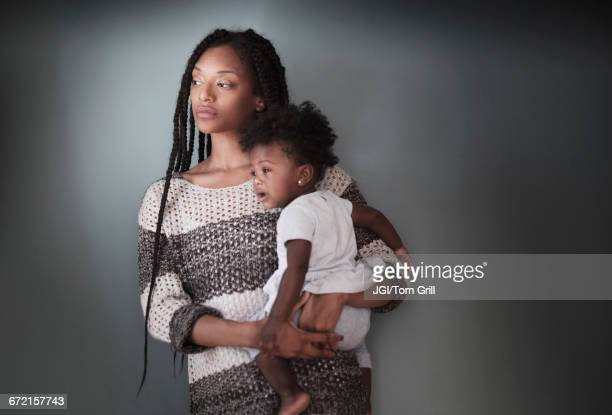 Thoughtful Black woman standing holding baby daughter