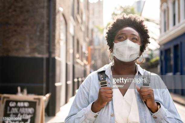 thoughtful black woman wearing a facemask on the street - protective face mask stock pictures, royalty-free photos & images