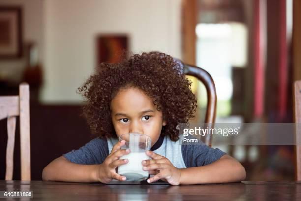 Nachdenkliche junge Trinkmilch zu Hause