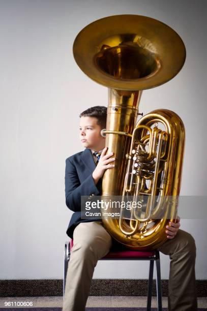 Thoughtful boy holding tuba while sitting on chair against white wall