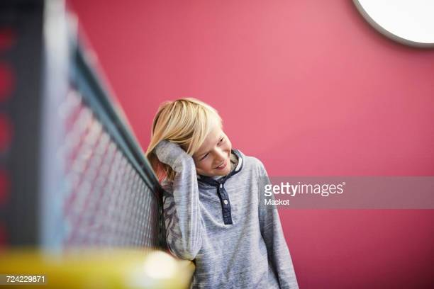 Thoughtful boy leaning on railing at middle school