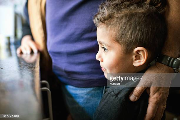 Thoughtful boy looking away while standing by father in kitchen