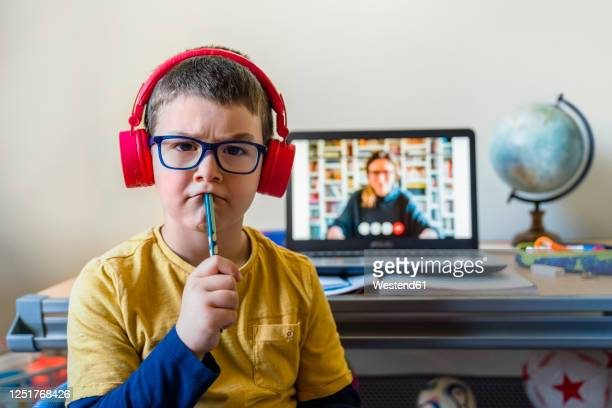 thoughtful boy sitting against laptop during video call at home - mindzoom 2 stock pictures, royalty-free photos & images