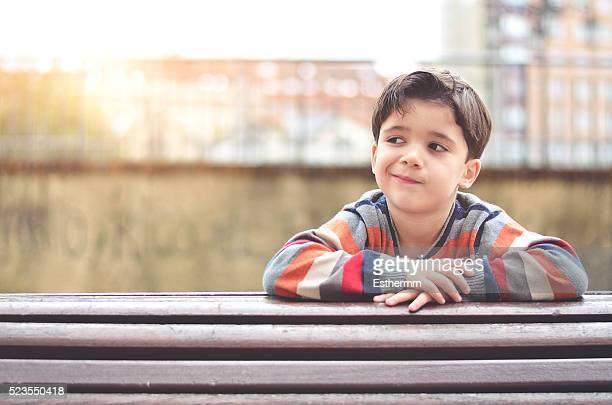 thoughtful boy sitting on a bench - demokratie stock-fotos und bilder