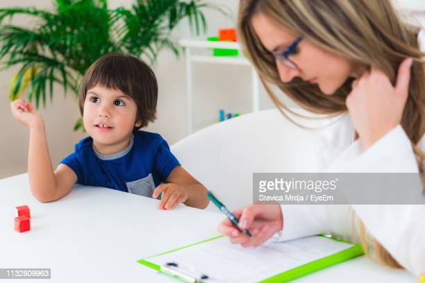 thoughtful boy sitting with female therapist at table in room - the_writer's_block stock pictures, royalty-free photos & images
