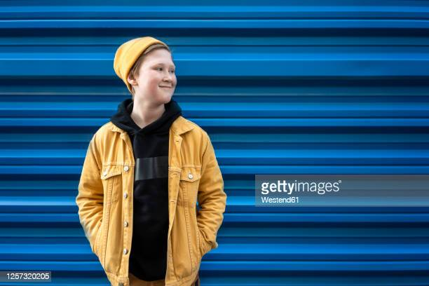 thoughtful boy smiling while standing against blue shutter during sunny day - coat stock pictures, royalty-free photos & images