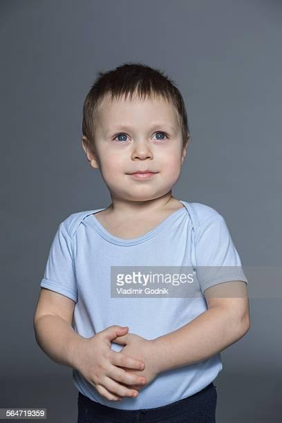 thoughtful boy with hands on stomach standing against gray background - handen op de buik stockfoto's en -beelden