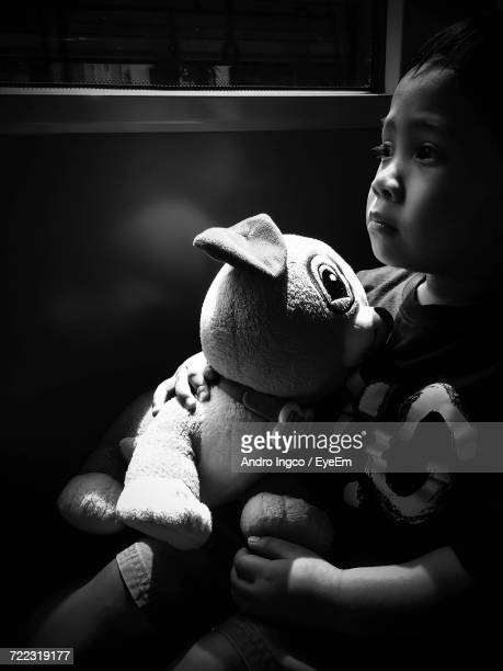 Thoughtful Boy With Stuffed Toy Sitting By Wall At Home
