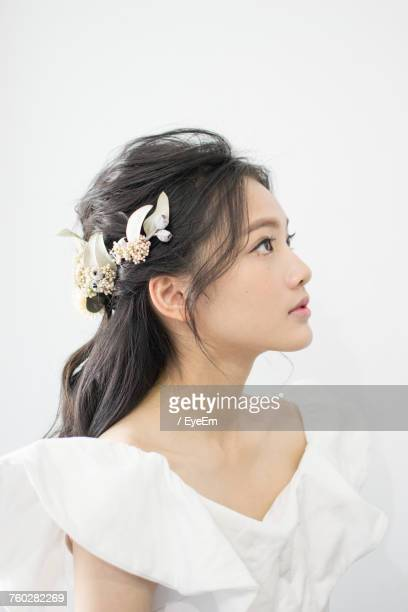 Thoughtful Bride Wearing Flowers On Hair Against White Background
