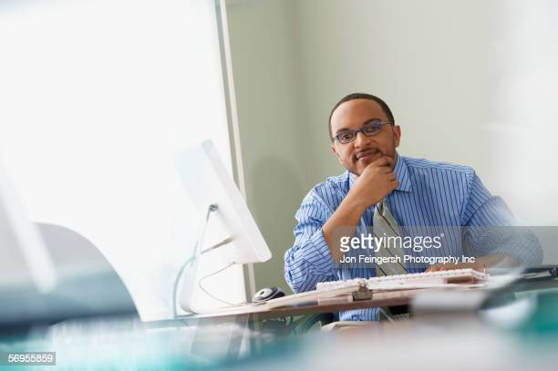 thoughtful businessman at desk - hand on chin stock pictures, royalty-free photos & images
