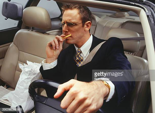Thoughtful businessman eating fries in car