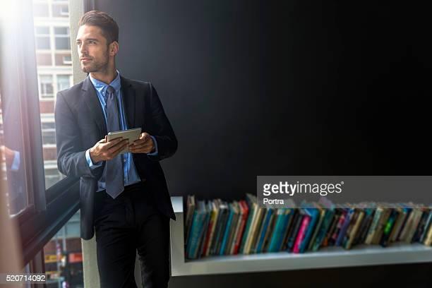 Thoughtful businessman holding digital tablet