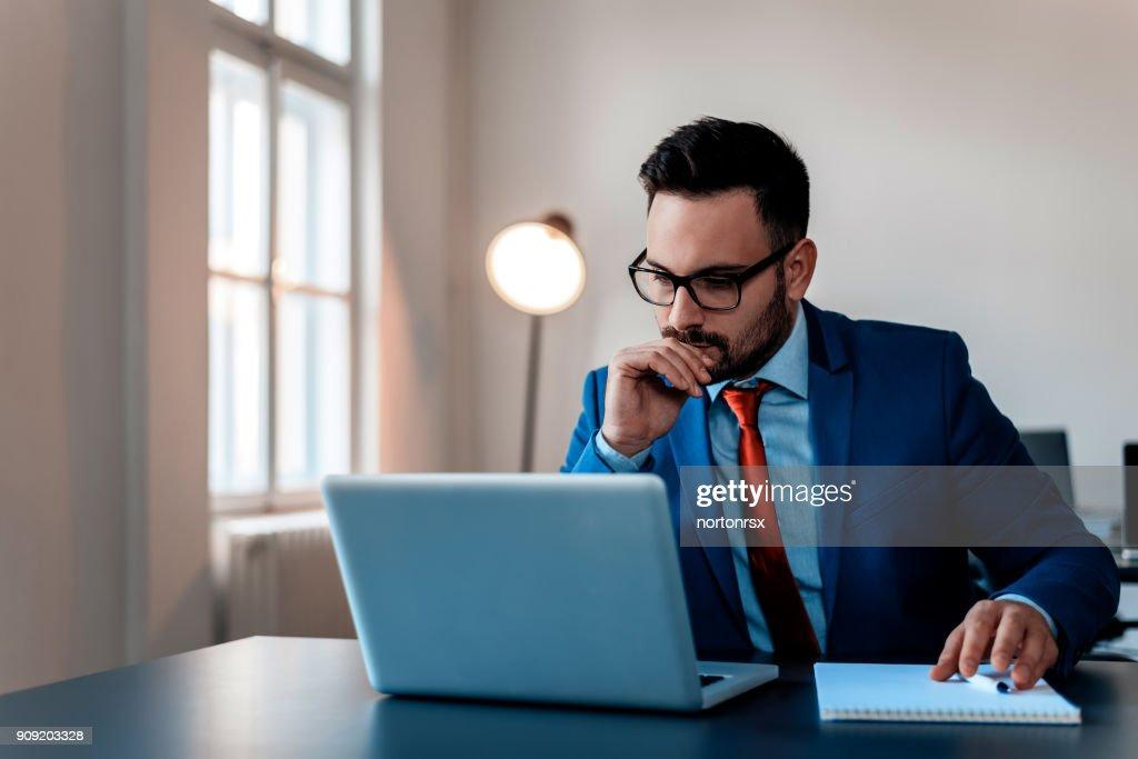 Nachdenklich Geschäftsmann im Büro, am Laptop arbeiten. : Stock-Foto