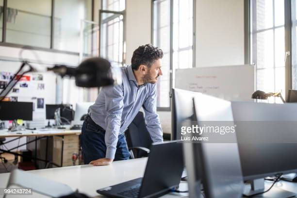 thoughtful businessman leaning on desk at office - konzentration stock-fotos und bilder