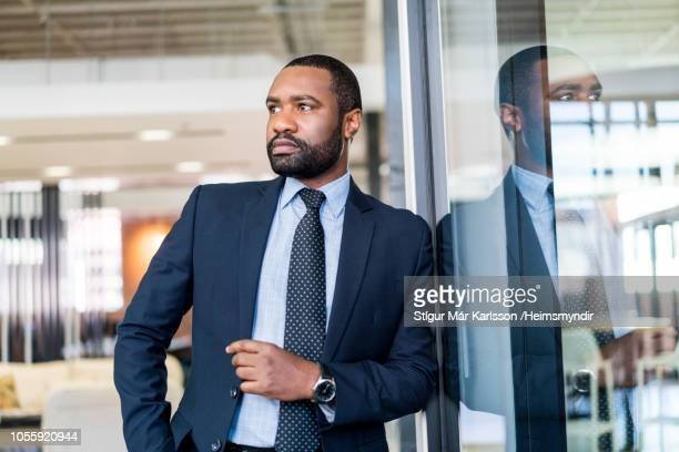 Thoughtful businessman leaning on glass at office