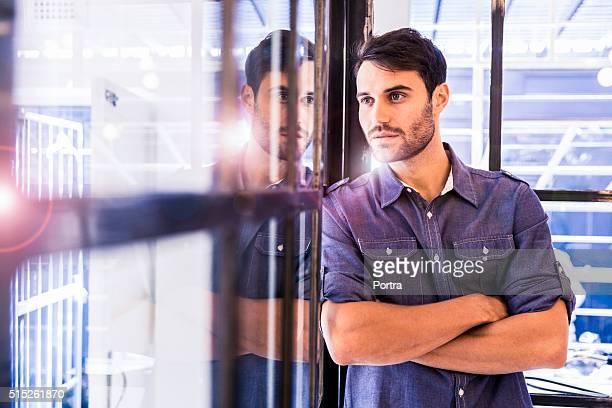 Hombre de negocios pensativo inclinado en la oficina de vidrio