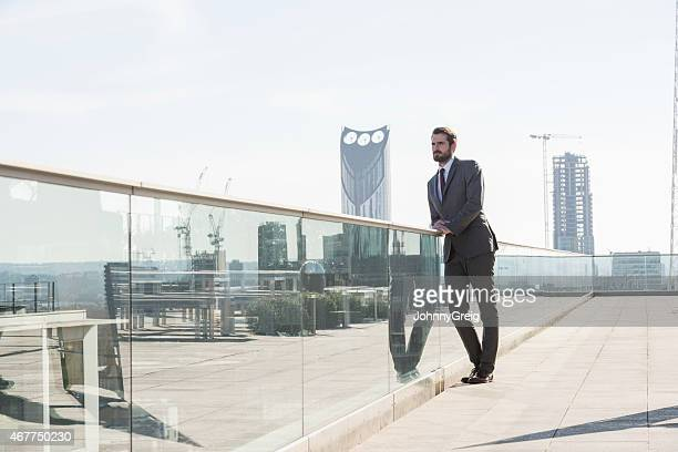 Thoughtful Businessman Leaning On Railing Against City Buildings