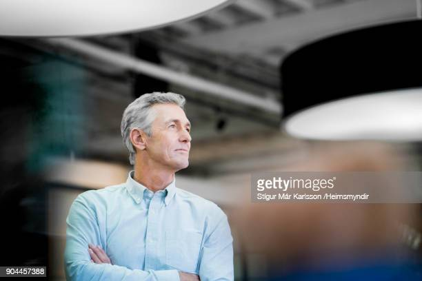 thoughtful businessman looking away at office - differential focus stock pictures, royalty-free photos & images
