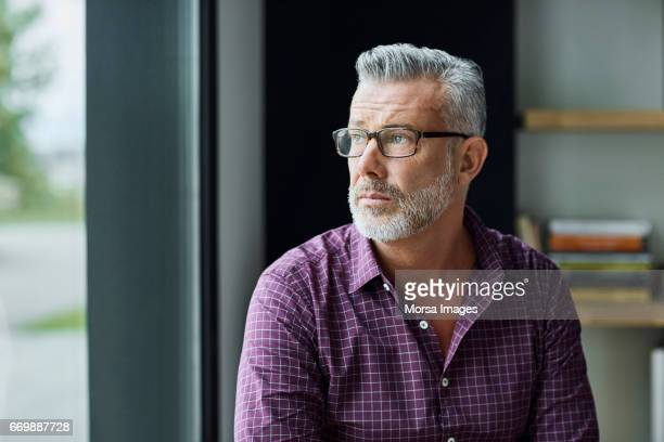 thoughtful businessman looking away in office - looking away stock pictures, royalty-free photos & images