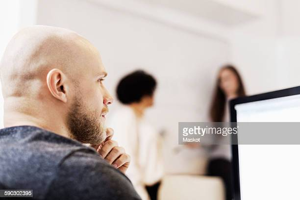 Thoughtful businessman looking away while colleagues discussing in background at office