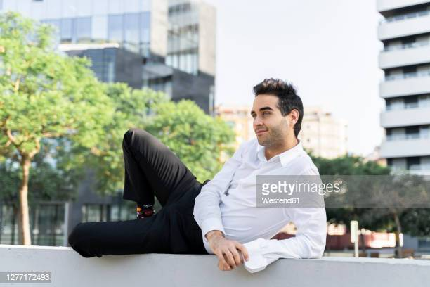 thoughtful businessman looking away while lying on retaining wall in city - lying on side stock pictures, royalty-free photos & images