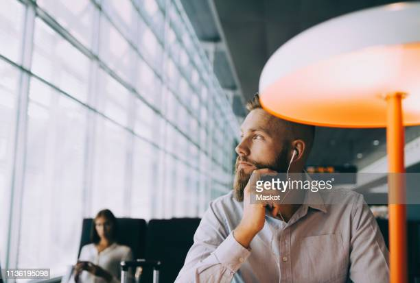 thoughtful businessman looking away while sitting at airport departure area - gate fotografías e imágenes de stock