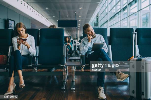 thoughtful businessman looking away while sitting by female colleague at waiting area in airport - waiting stock pictures, royalty-free photos & images
