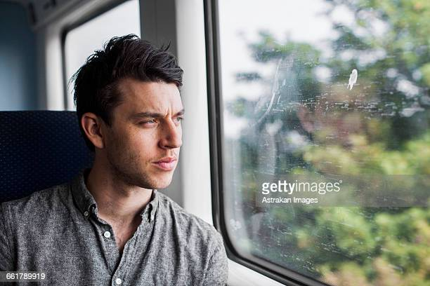 Thoughtful businessman looking through train window