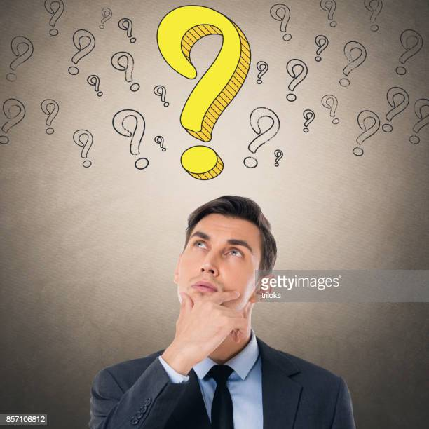 Thoughtful businessman looking up at question mark