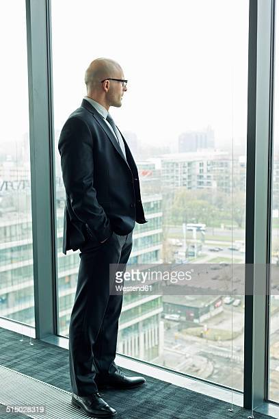Thoughtful businessman on office floor looking out of window