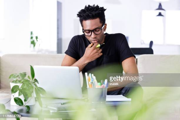 thoughtful businessman planning at table in office - izusek stock pictures, royalty-free photos & images
