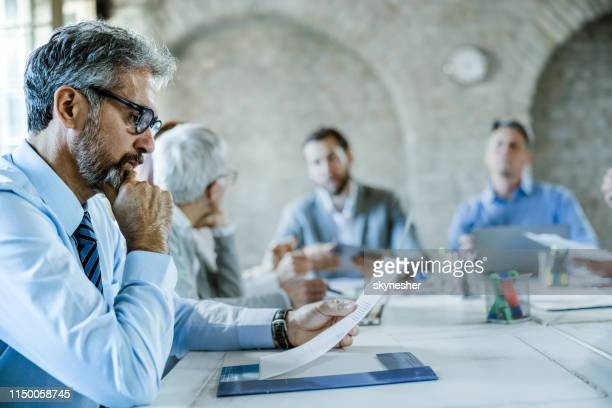 thoughtful businessman reading reports on a meeting in the office. - businesswear stock pictures, royalty-free photos & images