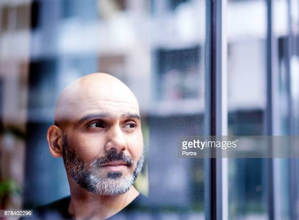 Thoughtful businessman seen through window