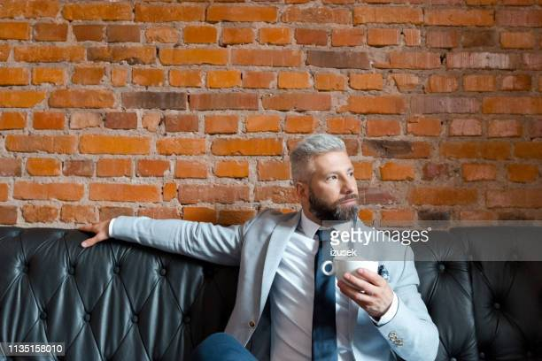 thoughtful businessman sitting in brewery - izusek stock pictures, royalty-free photos & images