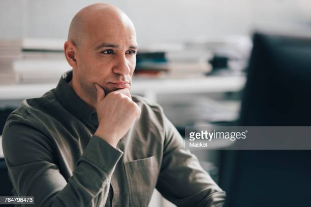 Thoughtful businessman sitting in front of computer monitor at office