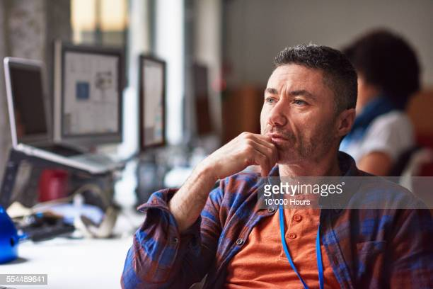 Thoughtful businessman sitting in start up office