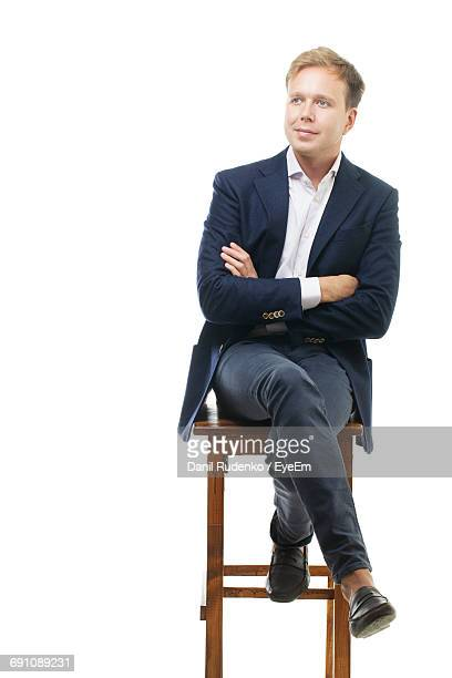 thoughtful businessman sitting on stool against white background - sitzen stock-fotos und bilder